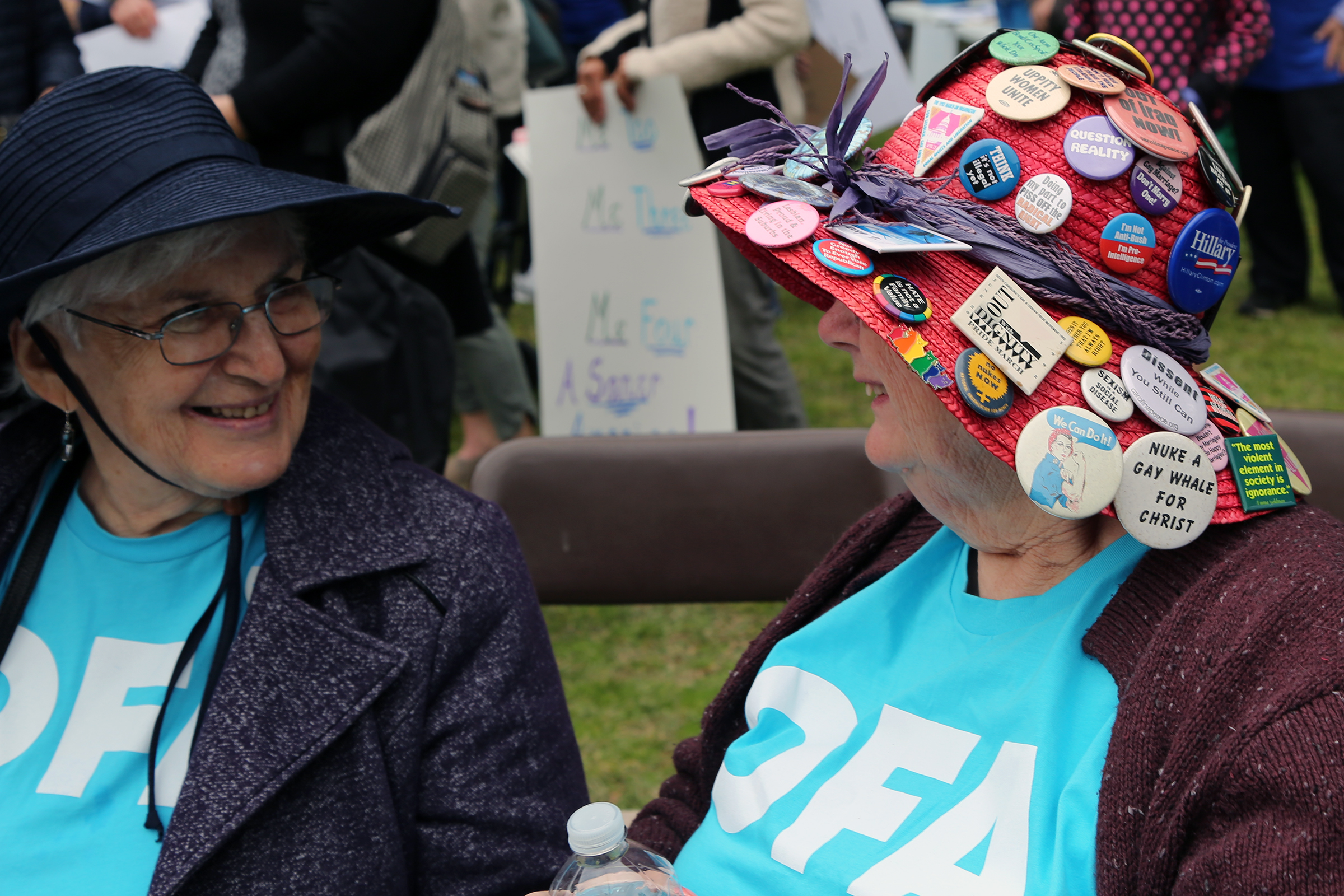 Nina Grey (left) and Peg Thompson (right) registered about 25 new voters at the march. Thompson has been collecting protest buttons for 40 years.