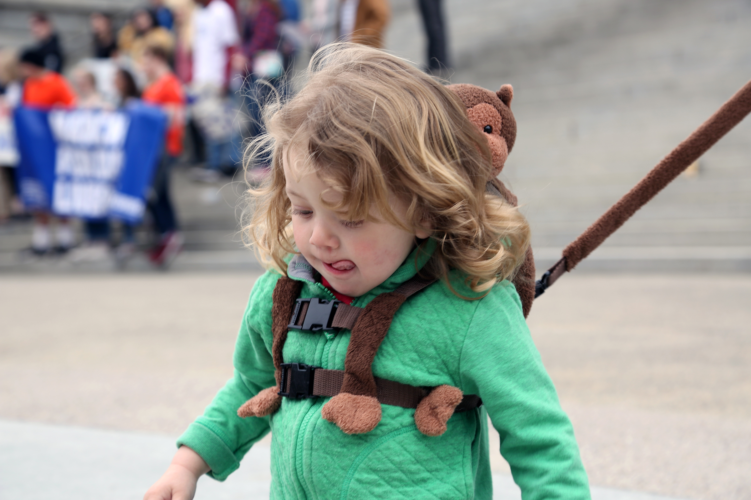Grandma brought this toddler to the march, using a leash to keep him within reach as he played on the State House steps.