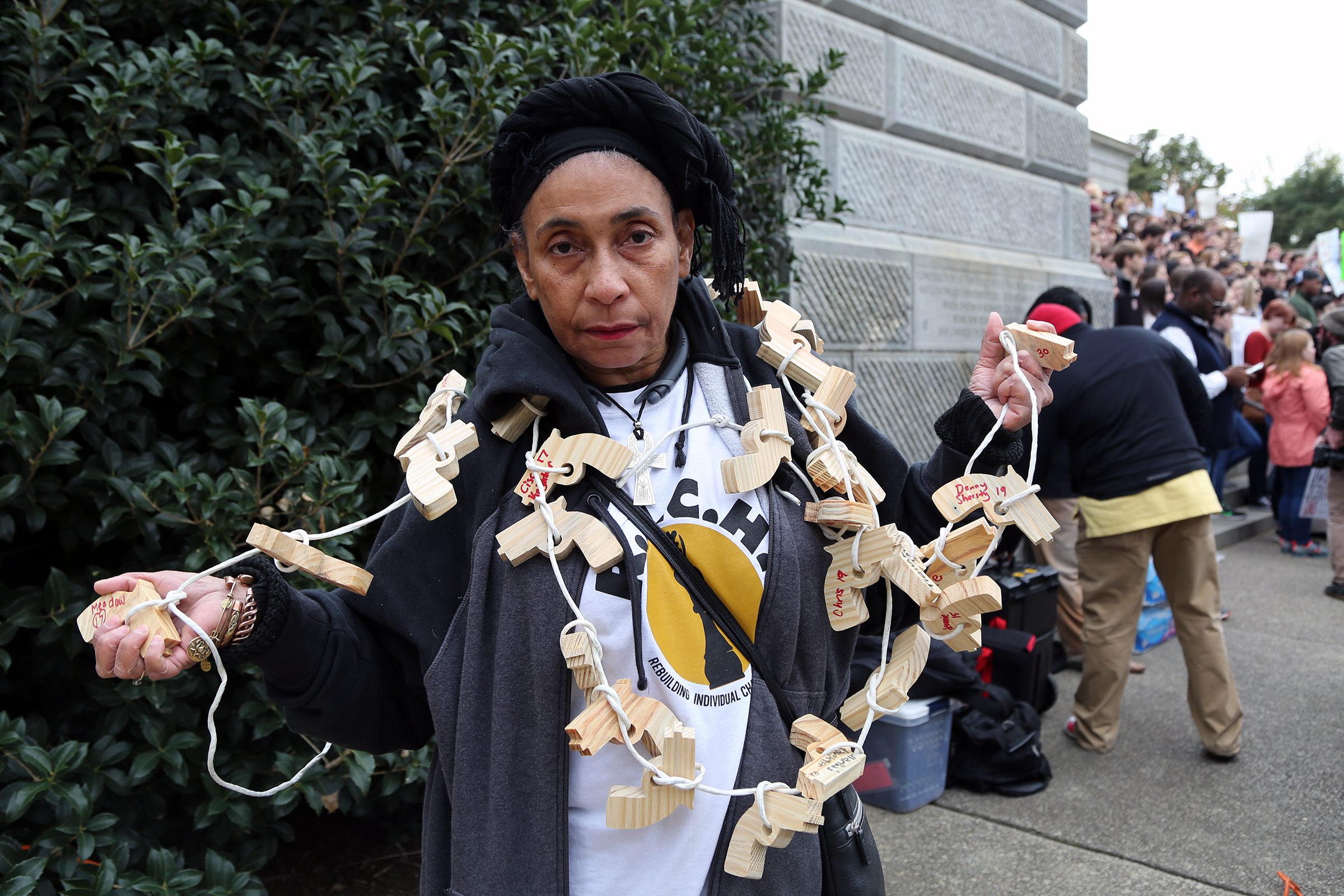 Mama G wore strands of wooden guns for relatives and friends of gun violence victims to sign. She estimated she's get about 50 signatures at the march.