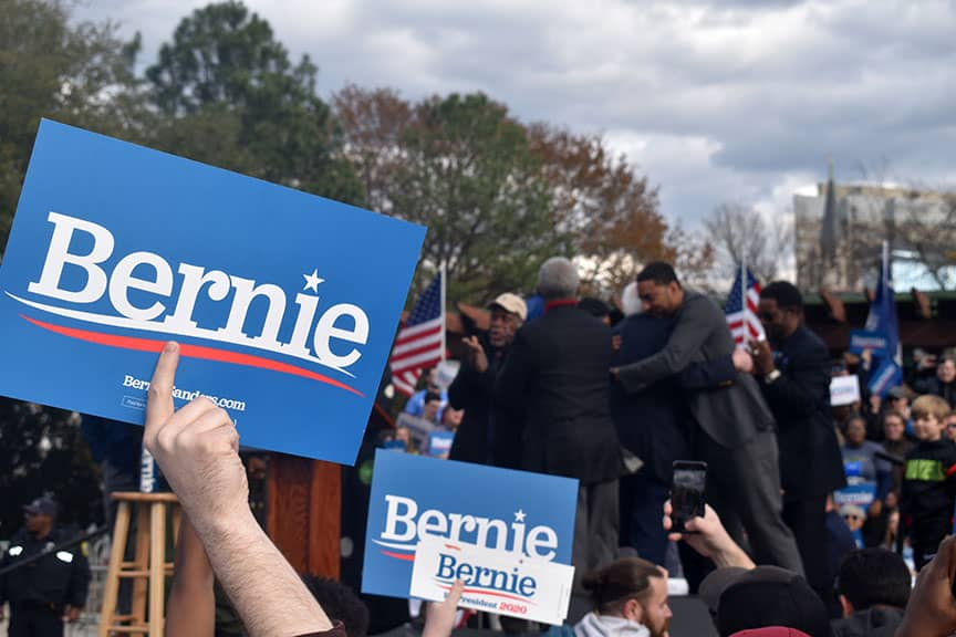 A Bernie Sanders supporter holds up a sign as the senator and speakers embrace each other on stage at Finley Park in Columbia, South Carolina.