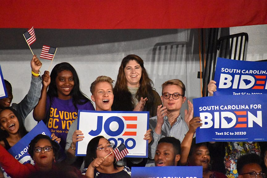 Joe Biden supporters hold signs and American flags as Biden speaks at primary night rally.
