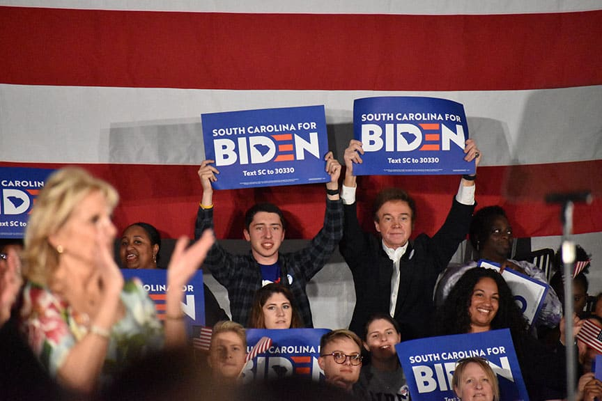 Biden supporters hold signs during his speech as Jill Biden claps.